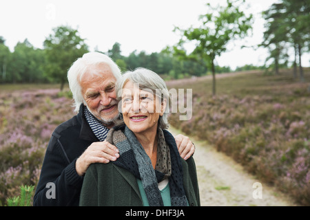 Pareja Senior, el hombre con las manos en los hombros de las mujeres