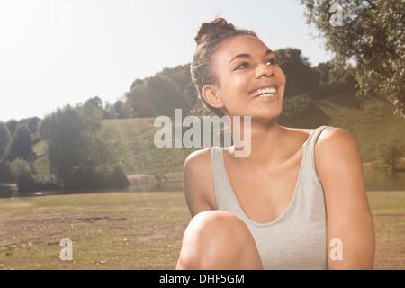 Feliz joven en la luz del sol en un parque