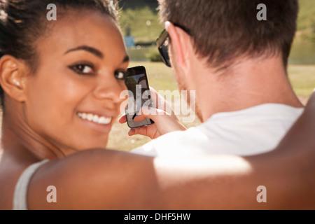 Pareja joven tomando imagen de sí mismos con teléfono, mujer mirando por encima del hombro