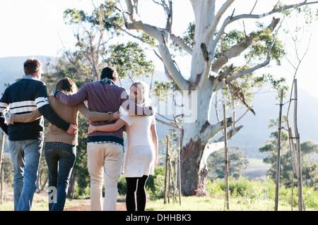 Amigos caminando por el campo con los brazos alrededor de Foto de stock
