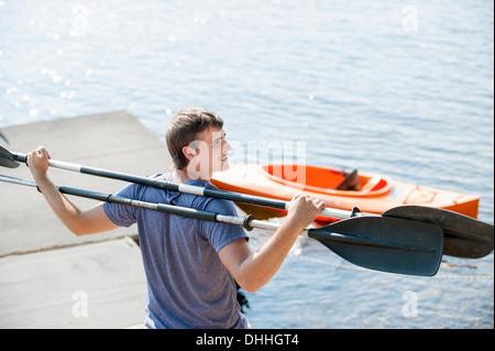 Joven celebración canoa remos en los hombros