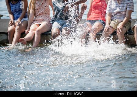 Amigos sentado en jetty chapoteando en el lago