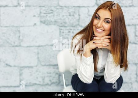 Hermosa joven empresaria sentado en la silla de oficina