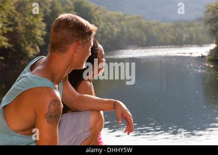 Pareja joven sentada por río, Hamburgo, Pennsylvania, EE.UU. Foto de stock