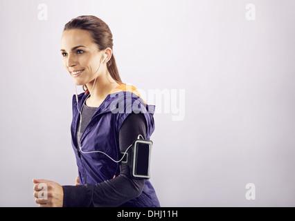 Imagen de bella mujer joven feliz corriendo y escuchando música en el fondo gris. Corredoras corriendo y sonriente. Foto de stock