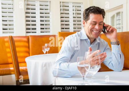 Empresario del Cáucaso en el móvil en el restaurante