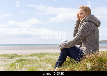 Atractiva mujer sentada en la playa Foto de stock