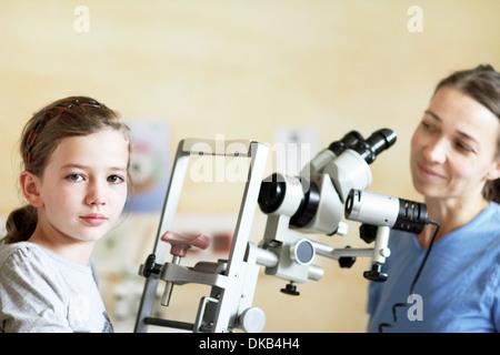 Optometrista preparando para examinar los ojos de la chica