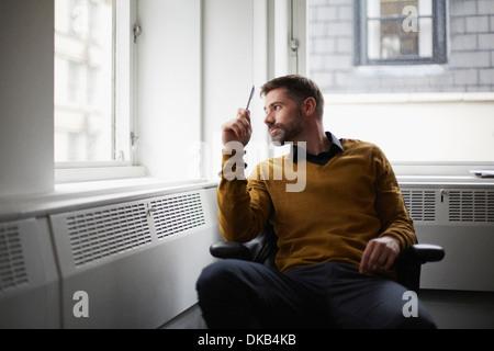 Empresario casual mirando afuera de la ventana