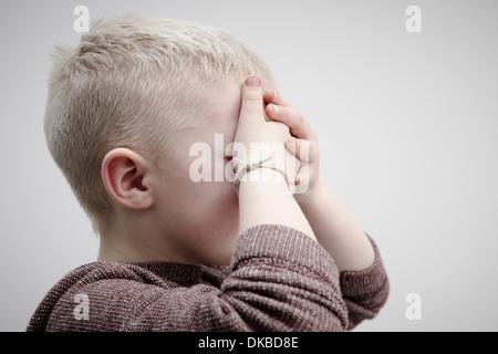 Retrato de niño usando brown puente, cubriendo la cara con las manos
