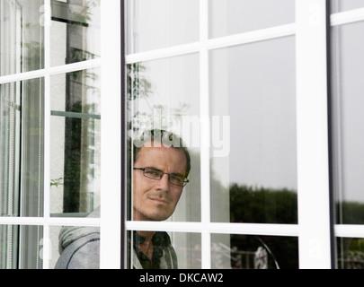 Retrato de mediados del hombre adulto mirando hacia afuera de la ventana