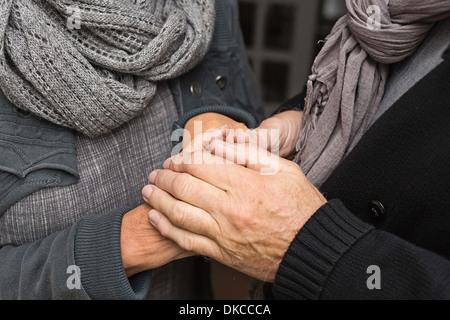 Senior pareja tomados de las manos, cerrar