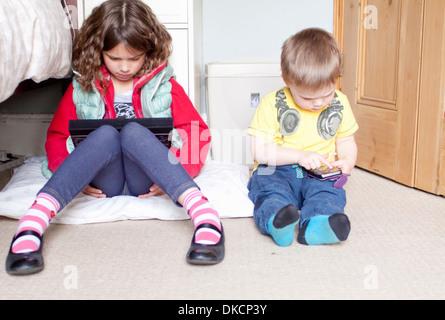 Los niños con digital tablet y teléfono móvil