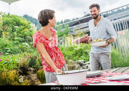 Pareja joven preparando la comida de picnic, Tirol, Austria
