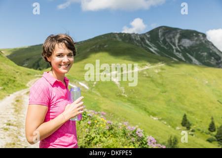 Mujer joven excursionista con agua embotellada, Tirol, Austria
