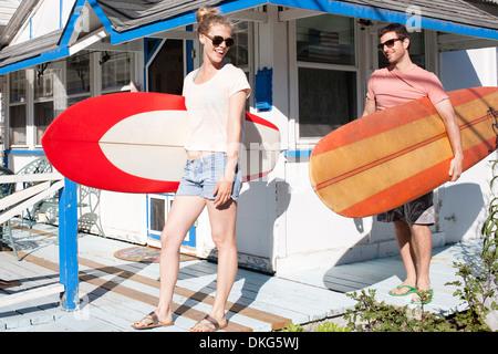 Pareja en el patio llevar tablas de surf, Breezy Point, Queens, Nueva York, EE.UU.