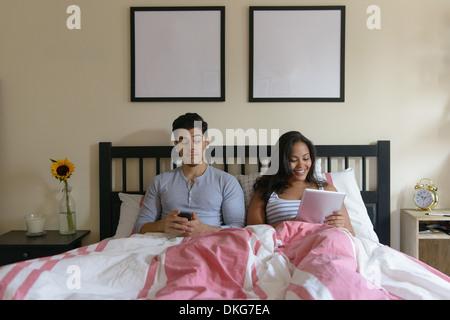 Pareja joven acostado en la cama, utilizando smartphones y tablet digital