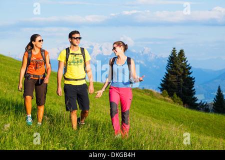 Los jóvenes senderismo de montaña en prados alpinos en el grupo Osterhorn, Estado de Salzburgo, Austria