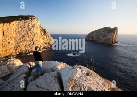Mujer disfrutando de la puesta de sol, Capo Caccia, Provincia Nurra, Cerdeña, Italia, Mediterráneo, Europa