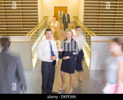 La gente de negocios en el corredor de oficina ocupado Foto de stock