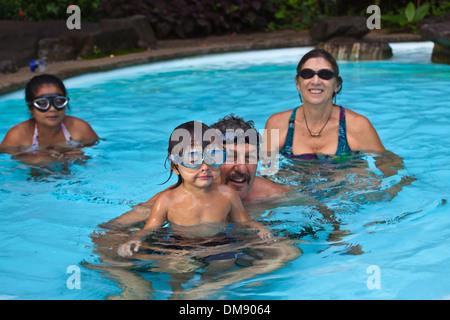 Un joven tailandés de media la mitad de los niños estadounidenses de natación con su madre y sus abuelos. Foto de stock