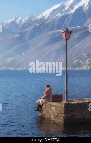 Una mujer con un abrigo rosa está sentado sobre un muelle en un lago
