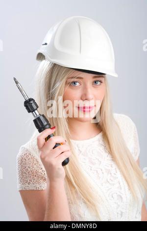 Bonita rubia mujer vistiendo un casco y sosteniendo un destornillador.