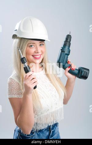 Bonita rubia mujer vistiendo un casco y sosteniendo un destornillador y un taladro.