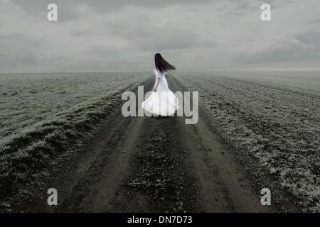 Mujer en vestido blanco está solo en un camino de tierra