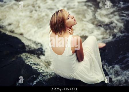 Mujer joven en vestido blanco sentado sobre un arroyo