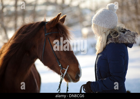 Mujer joven con caballo en invierno Foto de stock