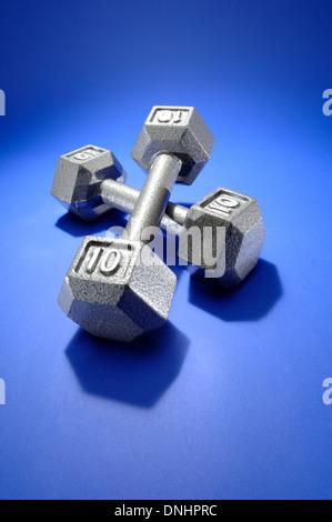 Un par de ejercicios de pesas metálicas sobre una colchoneta de ejercicios azul.