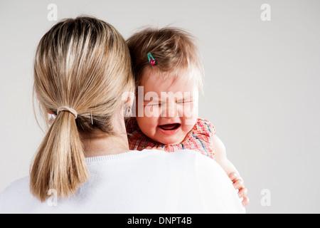 Vista sobre el hombro de la madre sosteniendo el llanto del bebé niña, Foto de Estudio