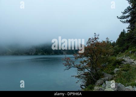 Las nubes bajas colgando sobre el lago de Gaube en la Vallee de Gaube en los pirineos franceses