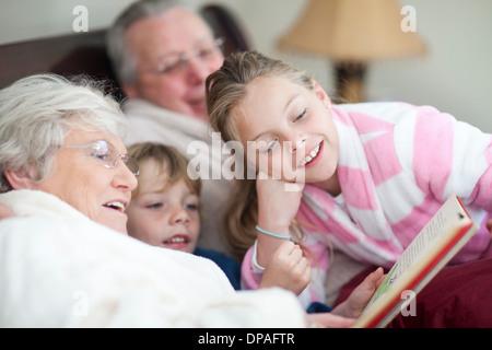 Abuelos y nietos leyendo cuentos de hadas en la cama