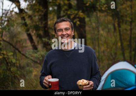 Hombre maduro en explotación forestal cupcake y bebida caliente