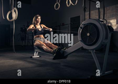 Mujer con máquina de remo en el gimnasio