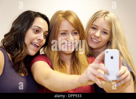 Selfie, siendo adoptada por tres jóvenes mujeres adolescentes niñas adolescentes en un Apple iPhone, Essex UK