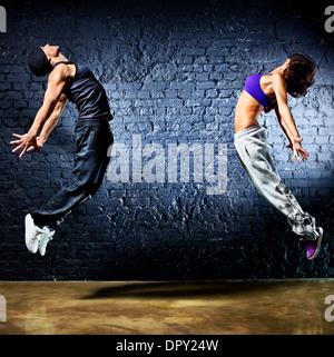 Pareja joven bailarín saltando. En la pared de fondo. Foto de stock