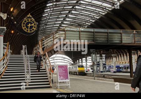 Interior de trainshed con techo de cristal y hierro, parado trenes & mujer caminando por plataforma reloj - York Railway Station, North Yorkshire, Inglaterra, Reino Unido.