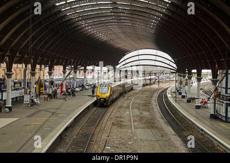Vista interior de trainshed con hierro y techo de cristal fijo, trenes y gente esperando en la estación de tren de platfom - York, North Yorkshire, Inglaterra, Reino Unido.