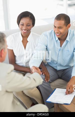 Sonriente joven pareja un apretón de manos con el vendedor en el sofá Foto de stock