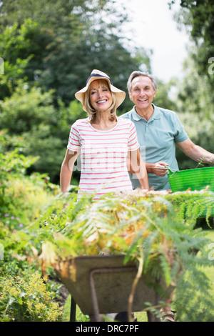 Las parejas ancianas con carretilla de mano y la cuchara en el jardín