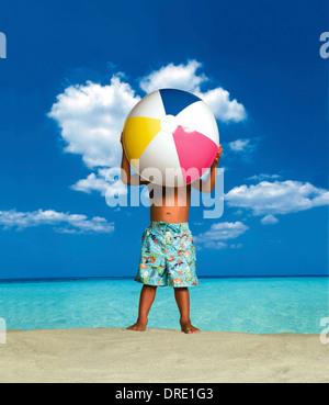 Chico en la playa sosteniendo un balón de playa