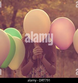 Chica se esconden detrás del globo. Retrato artístico