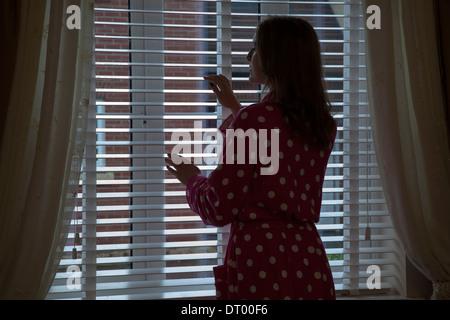 Silueta de mujer vistiendo una bata mirando por una ventana durante la noche. A lo largo de hombro/vista lateral.