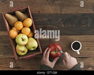 Una mesa de madera con una gran variedad de madera una caja de frutas frescas Peras y naranjas una persona cortando una manzana
