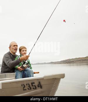 Un día en el lago de Ashokan un hombre mostrando un muchacho cómo pescar sentado en un barco