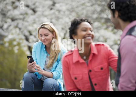 En la primavera del parque de la ciudad de Nueva York en los árboles en flor blanca una mujer sentada en un banco sosteniendo su teléfono móvil una pareja a su lado