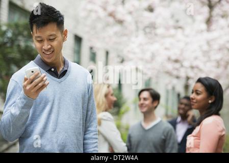 Vista sobre pueblo cityYoung al aire libre en un parque de la ciudad un hombre controlar su teléfono celular cuatro personas bajo un árbol en flor